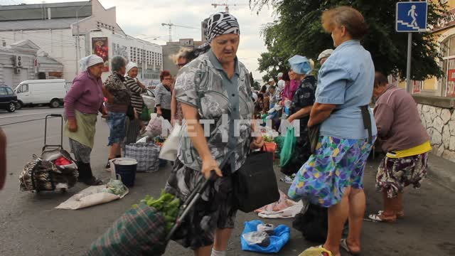Grandmother sell vegetables with it. Trade stalls, a farmers market, buyers, sellers, greens,...