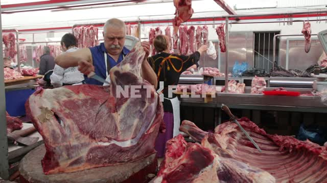 The mustachioed butcher expertly cut up the beef carcass. butcher, meat, beef, knife, skill,...