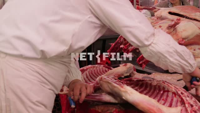 The butcher cut up the carcass on the market. Filmed from the back. meat, butcher, knife, carcass,...
