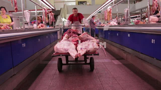 The butcher carries the carcass on the truck through the market. butcher, meat, market, truck, a...