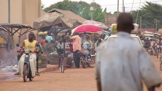 African market road, African people carry the products on the head, riding mopeds, motorcycles,...