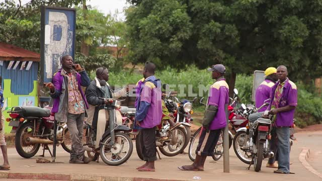 Men - Africans in the purple uniform standing near a motorcycle on the roadside. One of them is...