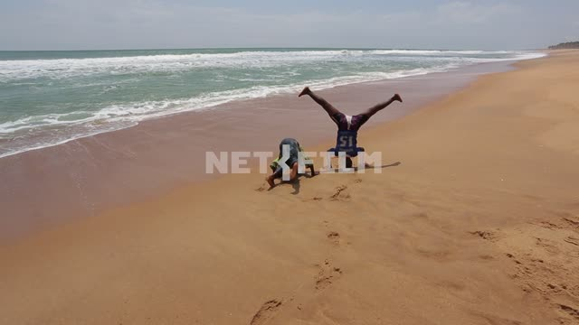 African children playing on the beach. African children, ocean, beach, children playing, headstand,...