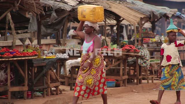 The African market, a woman with a girl teenager carries the products on the head. Africa, market,...