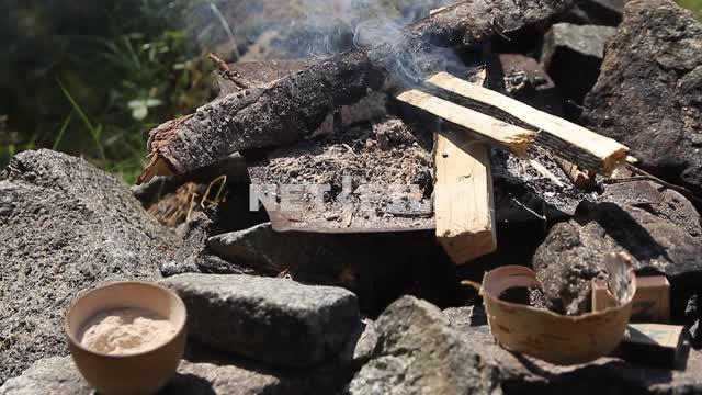 A small fire in the nature, near - ritual utensils, smoke, wood A small fire in the nature, near -...