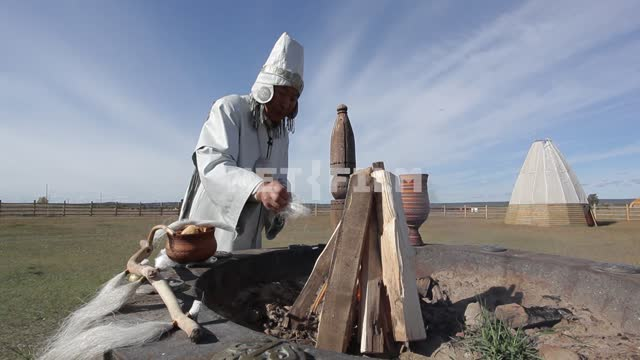 Yakut priest conducts the ceremony in a sacred place, bringing victims to the spirits, the kindling...