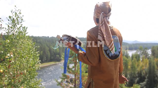 Shaman with a tambourine preparing for the ceremony on the high Bank of the mountain river Shaman...