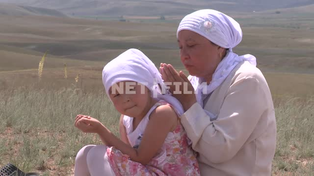 Prayer on the mountain, Women pray on the mountain top. A woman with a child sitting with folded...