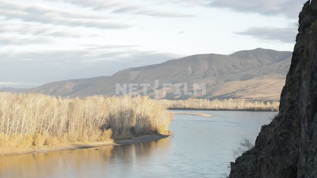 The shore of the wide river with yellow autumn vegetation, mountains in the distance. Sky, clouds,...