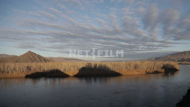 The shore of the wide river with yellow autumn vegetation. Mountains in the distance. Sky, clouds,...