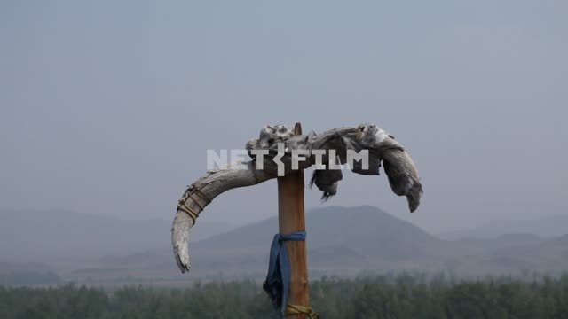 The skull of the animal on the ritual pole, river, mountains, sky, nature, Ethnography The skull of...