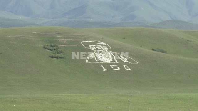 A giant portrait of an old man on the hillside, a modern geoglyph, mountain, sky, nature, clouds A...