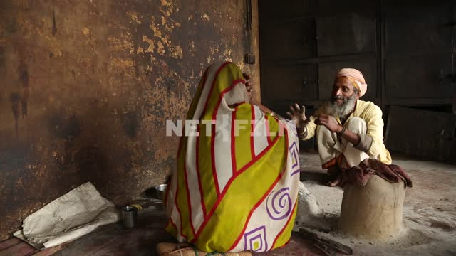 Indian woman and old Indian crematorium sitting talking animatedly Indian woman, Indian man,...
