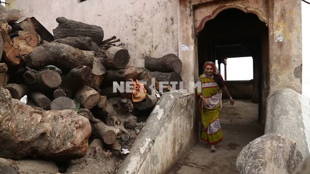 Indian woman comes out of the stone buildings on the street, stops in front of stacked firewood...