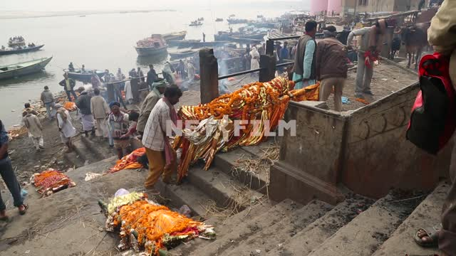 on the banks of the Ganges on the stone steps, dead men on the bamboo stretchers, the Indian men...