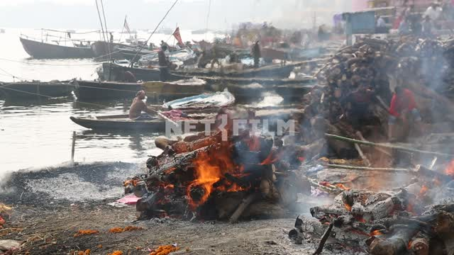 on the banks of the Ganges burning funeral pyres, the Indian men in the boats moor to shore the...