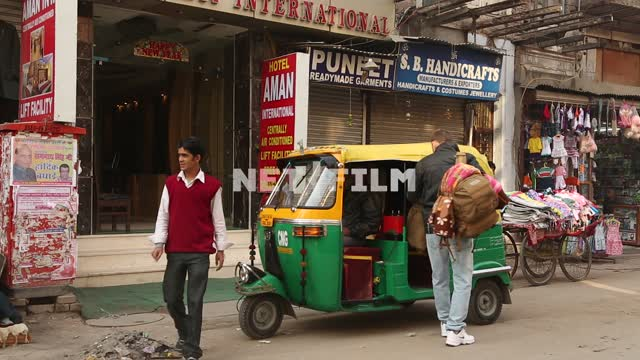 Indian calving out a male Caucasian with a backpack and sits down in an Indian taxi Indian hotel,...
