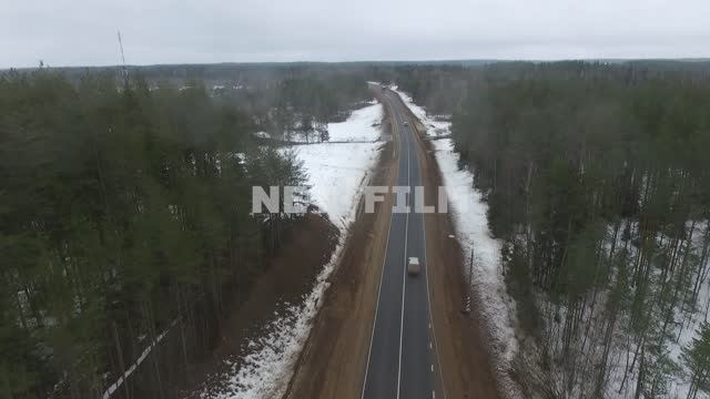 Top view car goes around the track in a snowy forest, crosses the bridge. Car, winter, drone,...