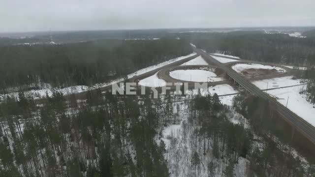 Top view of the motorway junction. Car, winter, drone, forest, pine, road, snow, stripes, road...