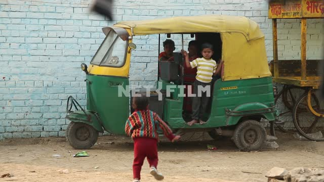 Children playing in an old and dirty tuk-tuk Children, slums, India, old tuk-tuk