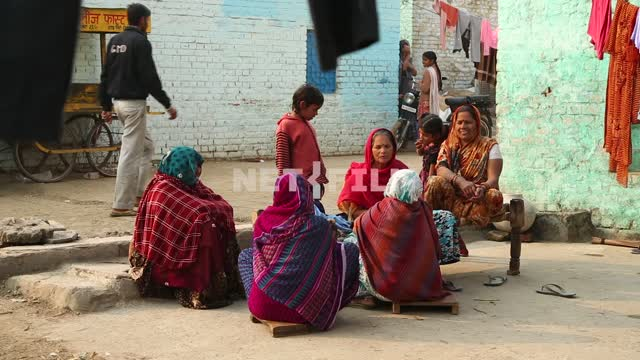 A few Indian women in traditional dress sit outside on a low wooden benches, next hung on a...