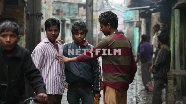 Young guys-the Indians are on a small street in the slums Young boys, Indians, street, slum