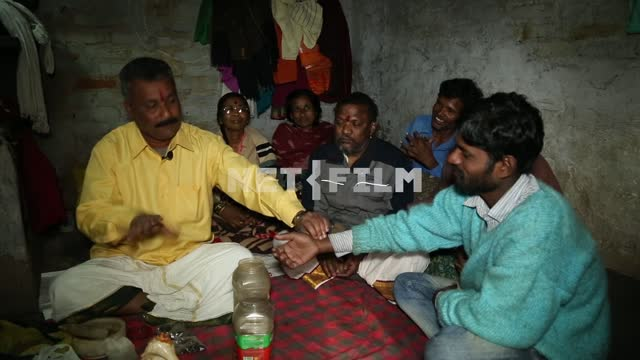Indian healer in the slums conducts reception of patients. around sitting patients The healer, the...