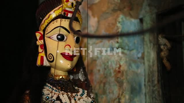Doll - Indian girl swinging on a thread on the backdrop of the picturesque ragged wall Doll -...