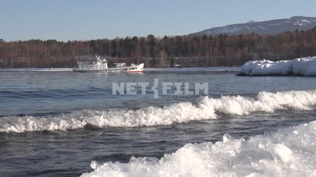 Lake Baikal, the waves are rushing on the shore, a ship is sailing to the shore Baikal, lake,...