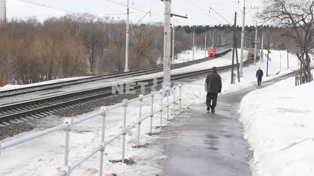 A person crosses railway tracks. Electric trains pass in different directions. People pass along...