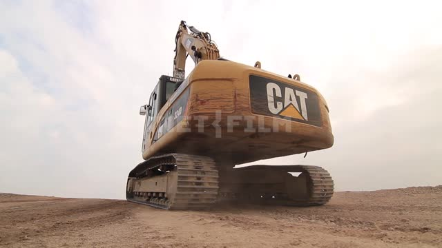 Excavator rides on the road Excavator, construction machinery, road machinery, road, dust