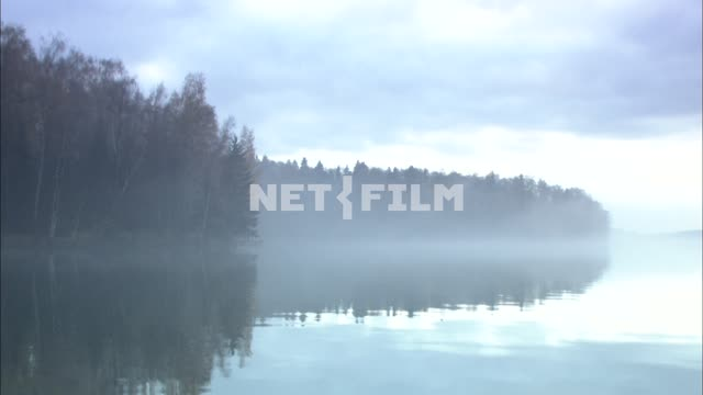 Lake and trees in the fog at dawn Nature. General plan. Fog Water River Reflection The autumn...