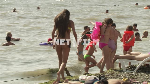 Holidaymakers on the beach near the sea The city. General plan. Sea. People are...
