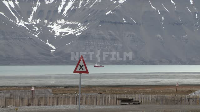 Mountain view by the sea and sailing ship. Russian North, mountains, snow, ship, traffic sign,...