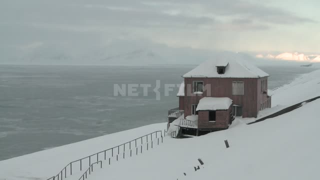 Wooden house over the sea, Russian North, sea, mountains, snow, clouds, hill, fence.