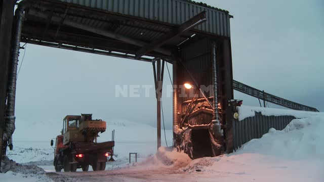 Machine - crane passing under the technical arch. Russian North, crane, arch, mine, snow.