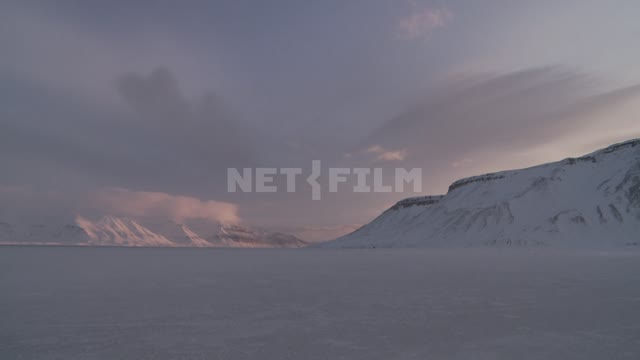 Views of the snowy plain and the mountains. Russian North, mountains, snow, clouds, wind, plain.