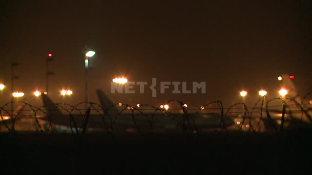 At night the planes are on the tarmac on the background of the lights of the airport. Airport,...