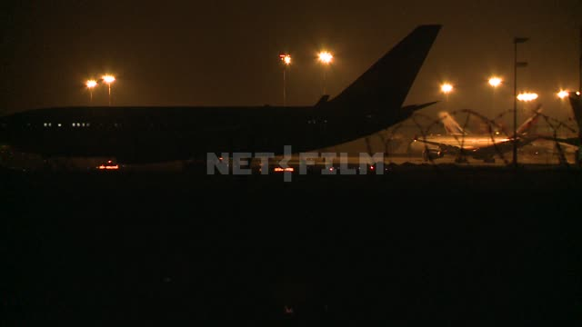 Night airfield tractor tows a plane on the tarmac. Airport, takeoff, airplane, spotlight, lights,...