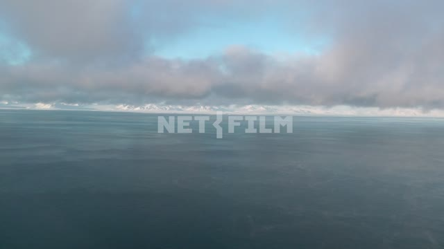 Shooting through the window of the helicopter and snow-capped mountains and the sea. Russian North,...