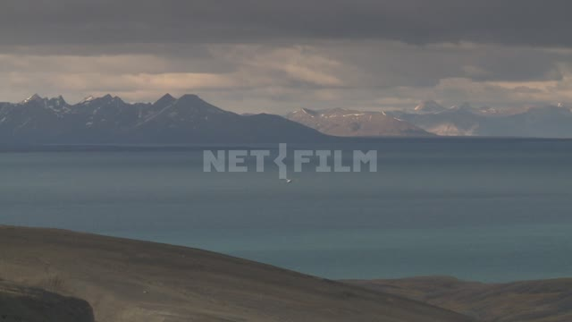 The sea and the mountains. Russian North, sea, mountains, seagulls, wooden building, clouds.
