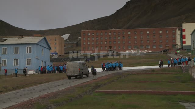 Tourists on the street in Barentsburg. Russian North, tourists, street, village, buildings.