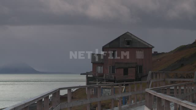 Wooden house on the shore. Russian North, house, sea, mountain, railing, bridges, clouds, clouds.