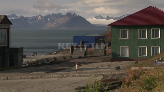 View of the buildings on the shore against the sea and mountains. Russian North, buildings, sea,...