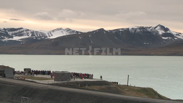 Views of snow-capped mountains and the sea, the people on shore. Russian North, shore, sea,...