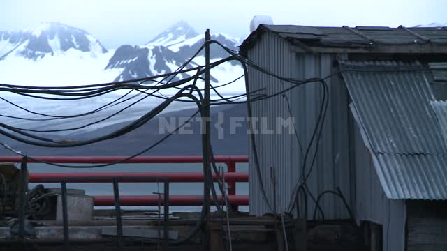 Pan with iron boxes power substation standing on the dock at the snow-capped mountains. Russian...