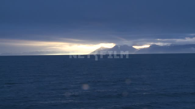 The view of the mountains from the sea. Russian North, mountains, sea, waves, sunset.