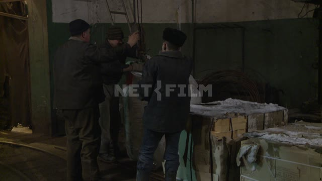 Workers install Packed goods on wooden pallet. Russian North, pallet, crane, cargo, worker.