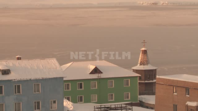 Houses and wooden Russian Orthodox Church in the village. Russian North.