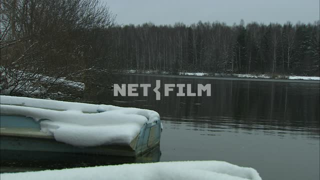 Boat under the snow on the river Bank. Snow, river, boat, shore, forest, water, autumn.